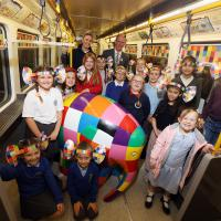 Pupils with their Elmer art work on board a Metro train