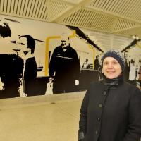 woman in front of byker station art work