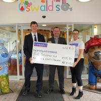 Nexus managers hand over a big cheque at St Oswald's