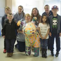 hospital staff and children with snow dog sculpture