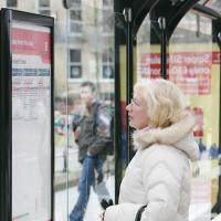 Commuter views bus shelter timetable