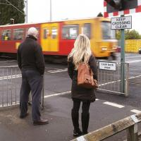 People standing at a level crossing