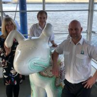 Ferry crew with Guide Dog Snowdog sculpture at the ferry landing waiting room in Siouth Shields