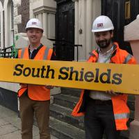 Museum and Nexus staff with the South Shields station sign in front of South Shields Museum