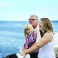A generic photo of a family on board the Ferry's top deck looking at the view of the Tyne