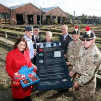 Nexus staff, Forces personnel show off the First World War memorial poster at a launch event