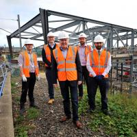 Cllr Iain Malcolm and workers next to the new steel work of the new bus and Metro interchange